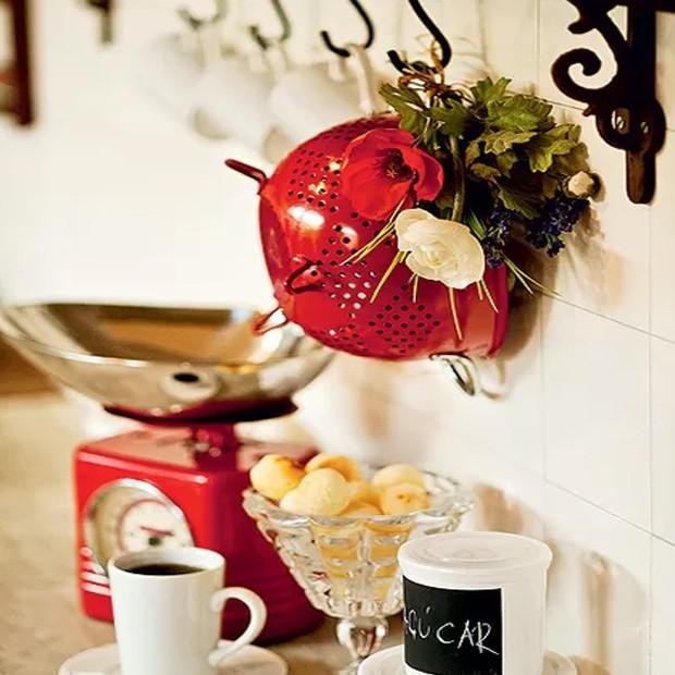 Pendurado na parede, o escorredor de macarrão serviu como base para um arranjo das versões artificiais de papoula, ranúnculo e lavanda. Um mimo! (Foto: Casa e Comida)