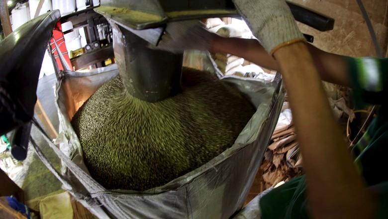 Trabalhador enchendo sacas de grãos de café para exportação em Santos, Brasil (Foto: REUTERS/Paulo Whitaker)