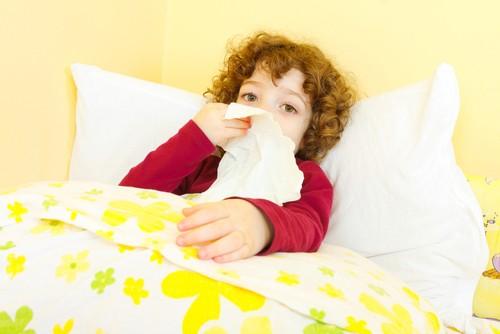Criança doente deitada na cama e assoando o nariz (Foto: Shutterstock)