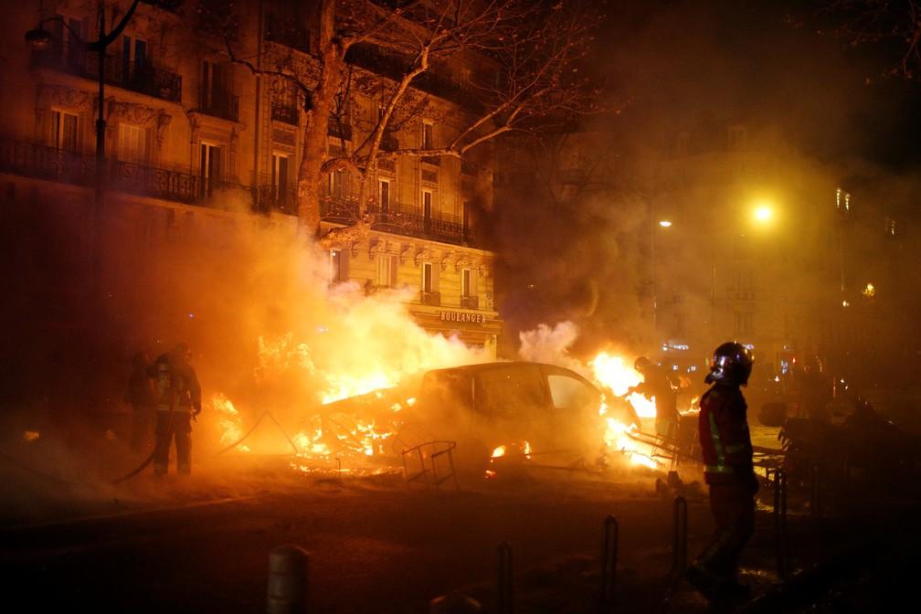 Bombeiros tentam apagar fogo em carro após manifestação dos coletes-amarelos em Paris — Foto: REUTERS/Stephane Mahe