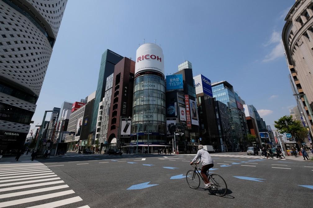 8 de abril - Homem de bicicleta passa por distrito comercial de Tóquio, no Japão, nesta quarta-feira (8)  — Foto: Kazuhiro Nogi / AFP