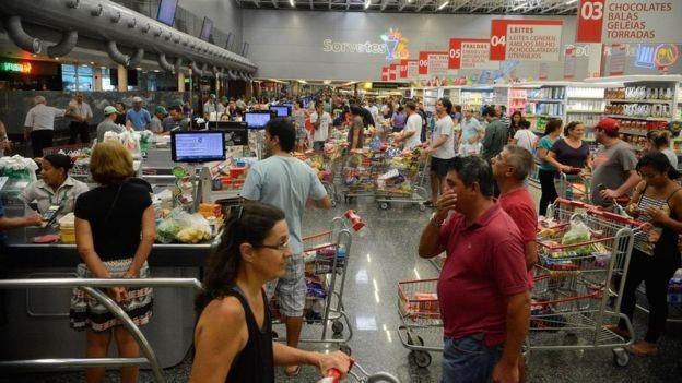 Entre gôndolas, prateleiras e esteiras de hiper e supermercados o comércio vê com mais intensidade esse tipo de reação (Foto: TÂNIA RÊGO/AGÊNCIA BRASIL via BBC News Brasil)