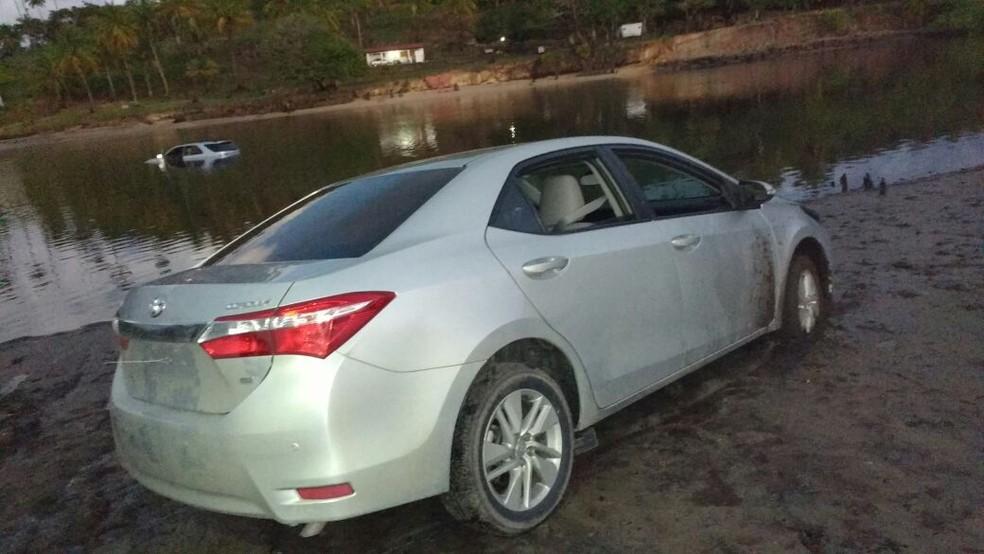 Um carro foi jogado na água e o outro ficou abandonado depois dos assalatos ocorridos em Tamandaré, em Pernambuco (Foto: Reprodução WhatsApp TV Globo)