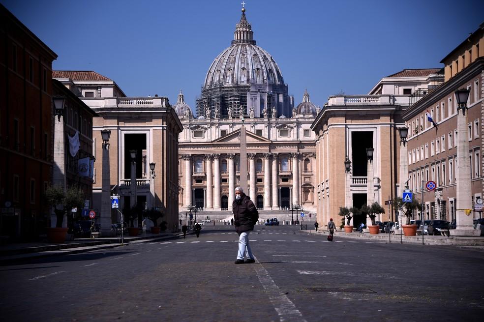 Homem caminha pela Praça de São Pedro, no Vaticano, nesta quarta-feira (8)  — Foto: Filippo Monteforte / AFP