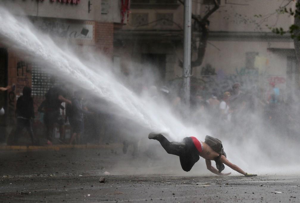 Manifestante é atingido por canhão d'água durante protesto contra o governo do Chile em Santiago na segunda-feira (11) — Foto: Ivan Alvarado/ Reuters