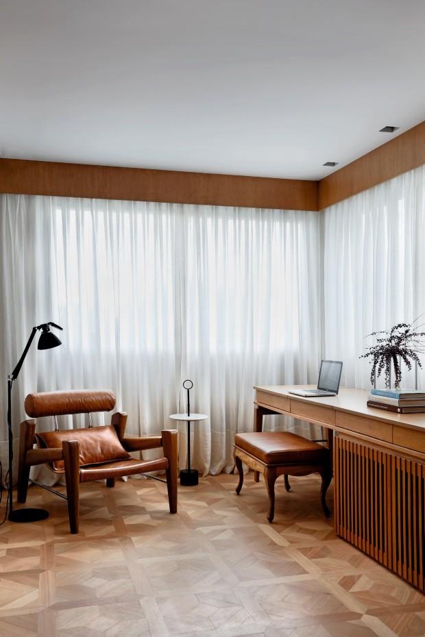 Na suíte, o móvel de tauari desenhado pelos arquitetos tem um pequeno canto de trabalho, com banco da Quartos Etc. O espaço de leitura compõe-se de poltrona de Zanini de Zanine, na Way Design, além de mesa lateral e luminária  (Foto: Denilson Machado / MCA Estúdio)