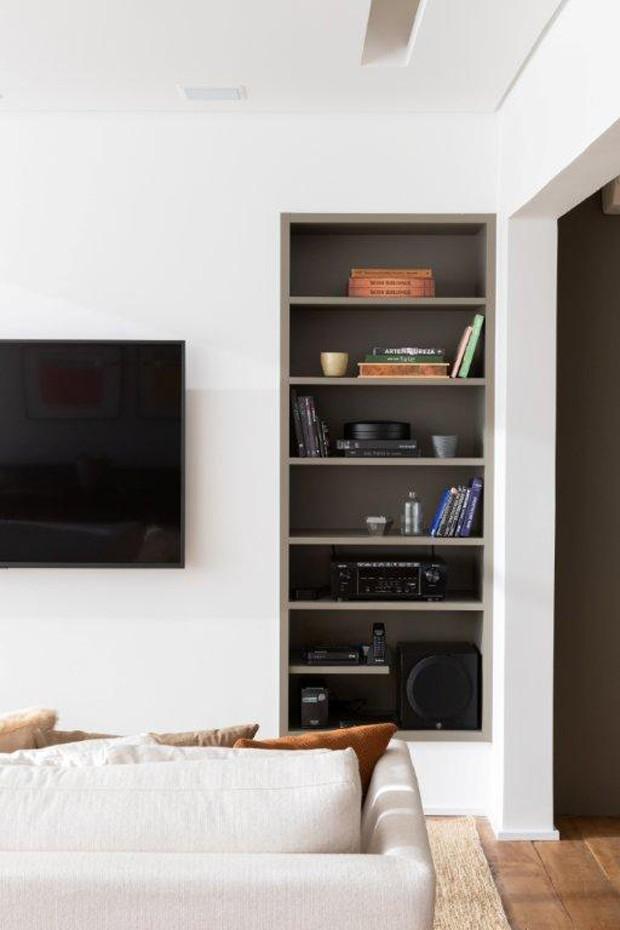 Para ganhar mais espaço para o sofá, o rack saiu de cena - todos os equipamentos eletrônicos ficam na estante embutida na parede (Foto: Alexandre Disaro/Divulgação)
