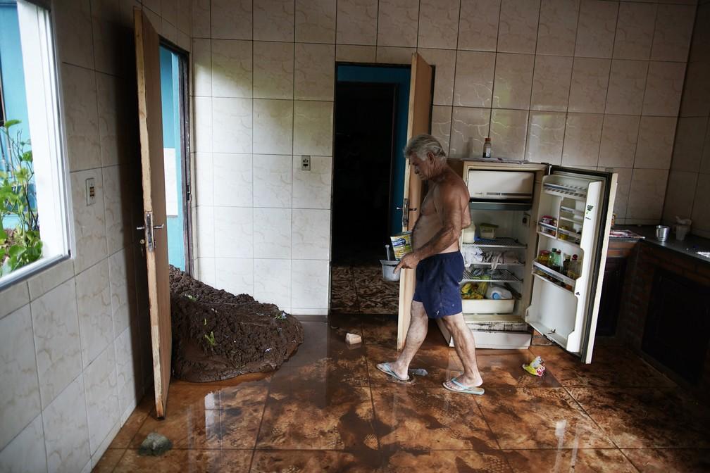 Darcy Brum anda em meio à lama que entrou na cozinha de seu sogro perto de Brumadinho, neste sábado (26), depois do rompimento da barragem da Vale. — Foto: Leo Correa/AP