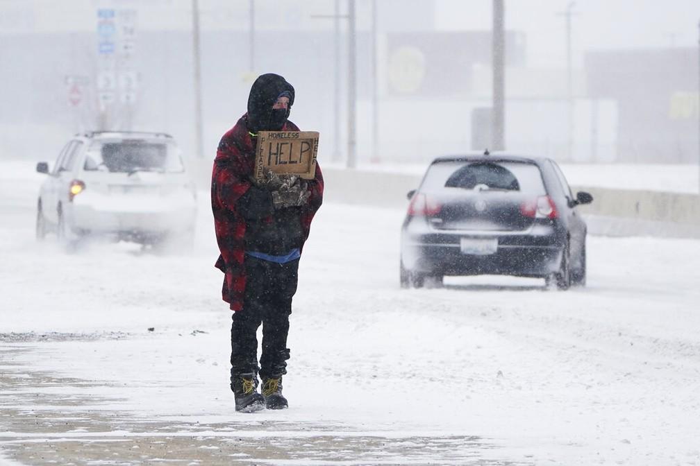 Desempregado após restaurante demitir em massa por causa da pandemia, homem pede dinheiro em uma rodovia de Oklahoma City (EUA) durante nevasca no domingo (14) — Foto: Sue Ogrocki/AP Photo