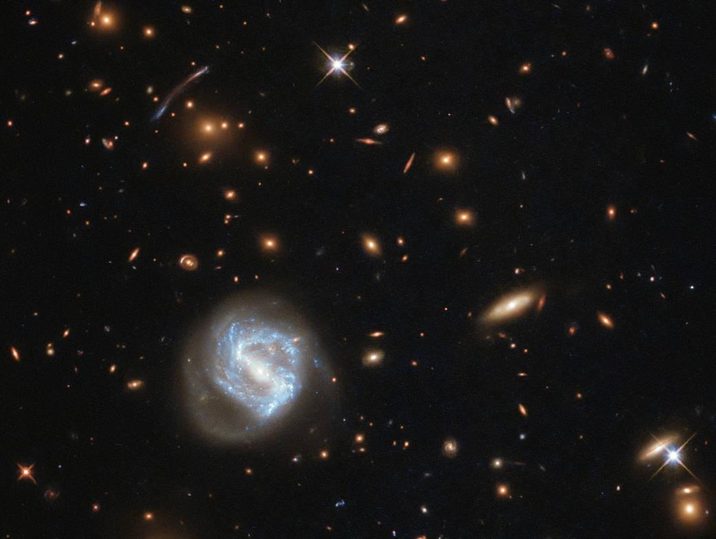 Aglomerado de galáxias (à esquerda), registrado pelo telescópio Hubble (Foto: Divulgação/ NASA)