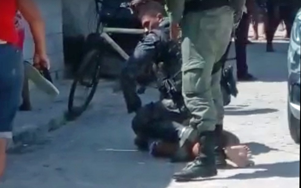 Policial militar imobilizando garota de 15 anos durante abordagem no Recife — Foto: Reprodução/WhatsApp