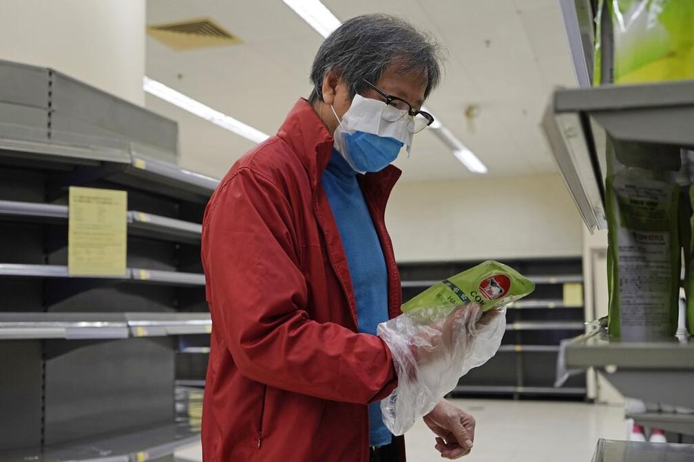 Homem veste máscara de proteção e usa uma sacola plástica como luva enquanto faz as compras em um supermercado de Hong Kong — Foto: Kin Cheung/AP