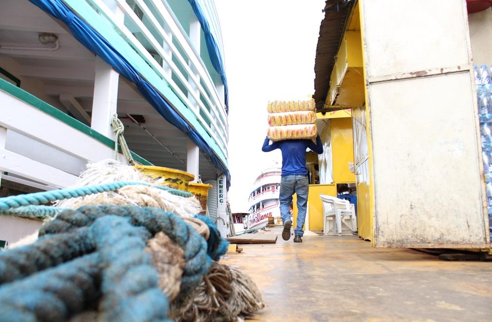 Carregador caminha entre lanchonetes e embarcação em balsa no Rio Negro, em Manaus (Foto: Leandro Tapajós/G1 AM)