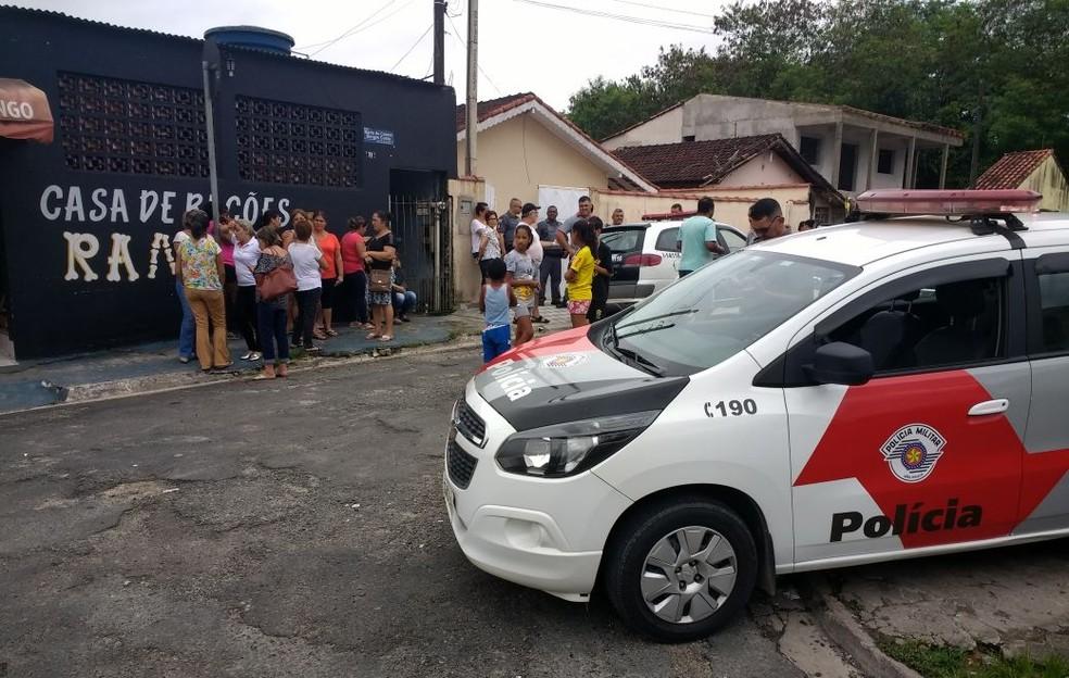 Populares observam a ação da polícia na casa onde viviam os idosos, no bairro Nosso Teto (Foto: Dione Aguiar)