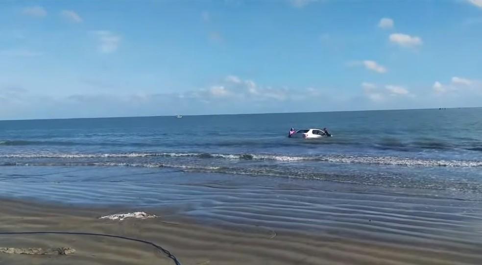 Carro foi achado dentro do mar, por moradores de Grossos, e tirado da água com ajuda de caminhonete.  — Foto: Ronaldo Josino/Reprodução