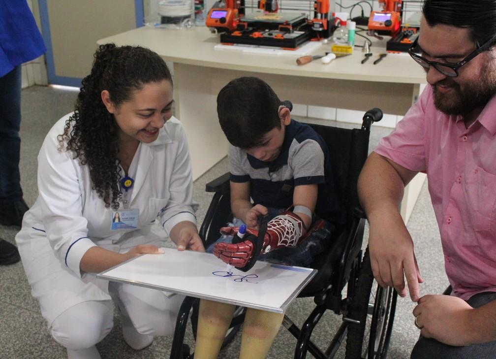 João Victor escreve o próprio nome durante sua primeira experiência com a prótese.  — Foto: Pedro Bentes/G1