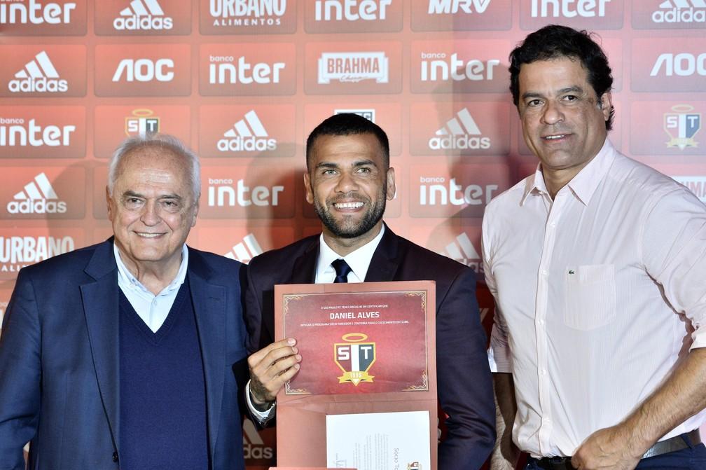 Daniel Alves ganha cartão de sócio-torcedor do São Paulo das mãos de Leco e Raí — Foto: Marcos Ribolli