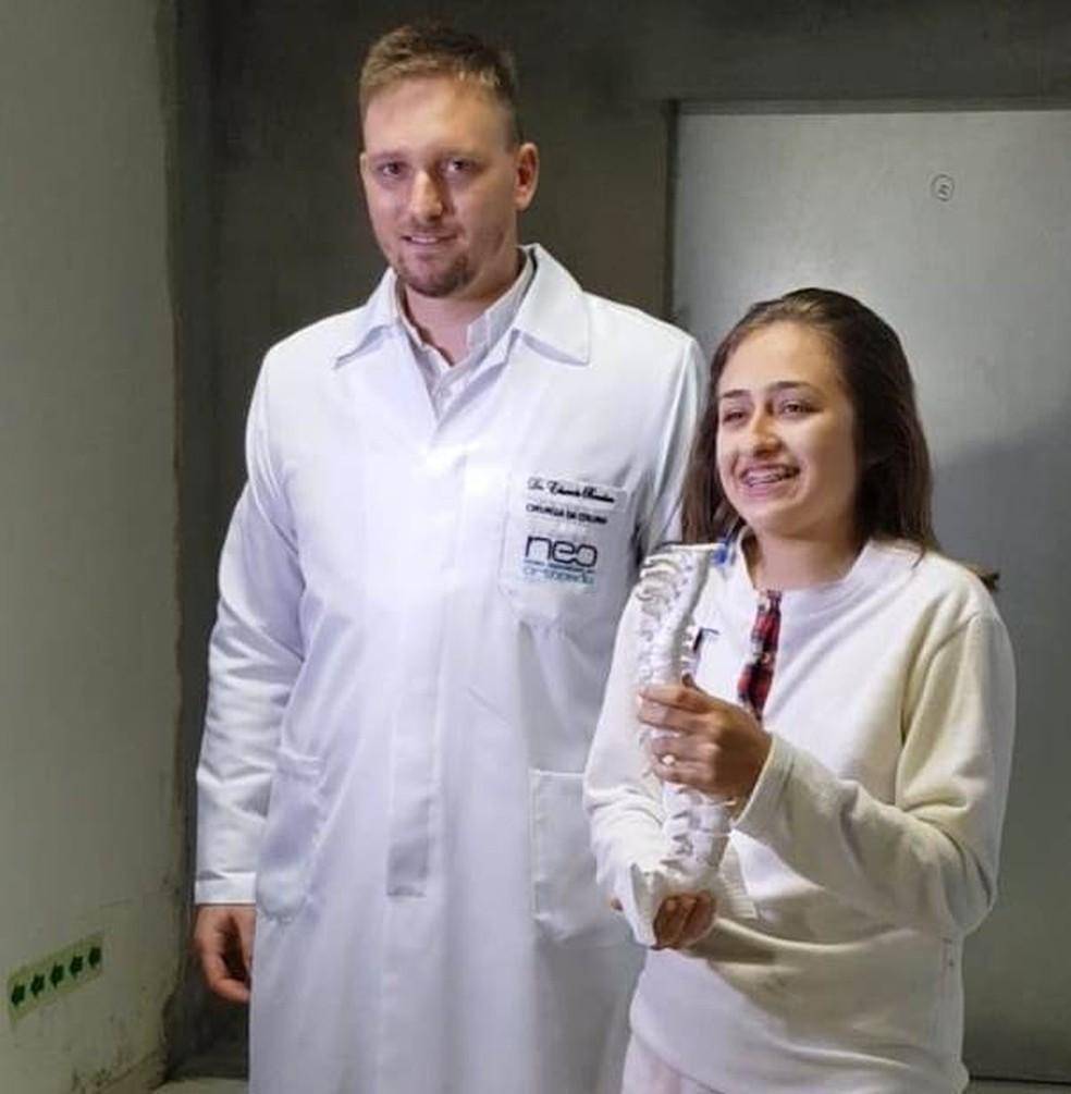 Júlia Spies e o médico Eduardo Bondan mostram o protótipo da coluna  — Foto: HRO/ Divulgação