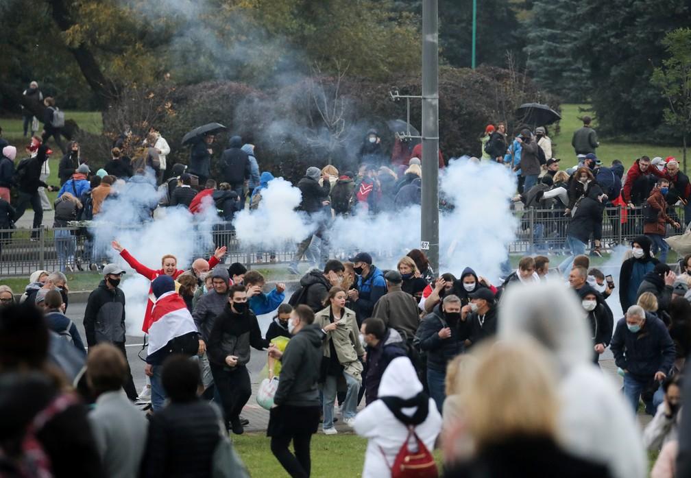 Manifestantes correm enquanto uma bomba de efeito moral explode durante um protesto da oposição para rejeitar os resultados das eleições presidenciais em Minsk, Belarus, neste domingo (11) — Foto: BelaPAN via Reuters
