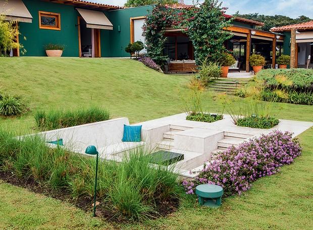 No meio do jardim, fica o fogo de chão, com almofadas de tecido para área externa. A realização da área é da GMC Arquitetura, que assina a construção e a decoração da casa (Foto: Felipe Gombossy/Divulgação)