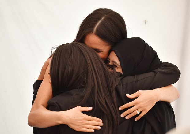 LONDON, ENGLAND - SEPTEMBER 20: Meghan, Duchess of Sussex embraces women at an event to mark the launch of a cookbook with recipes from a group of women affected by the Grenfell Tower fire at Kensington Palace on September 20, 2018 in London, England. (Ph (Foto: Getty Images)