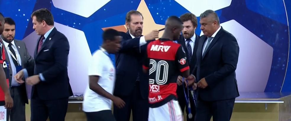 Vinicius Júnior pega medalha com a mão e não deixa que ela seja colocada no pescoço (Foto: Reprodução/SporTV)