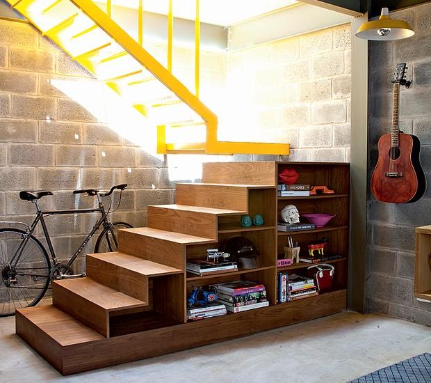 No projeto do escritório Arkitito, não só o espaço debaixo da escada é usado para guardar a bicicleta, como os degraus também são aproveitados. Na parte voltada para a parede, o morador guarda ferramentas e, na vista da sala, seus objetos de design (Foto: Maíra Acayaba)