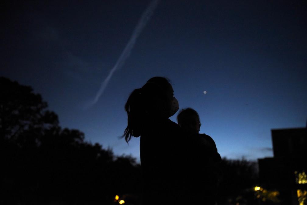 21 de dezembro de 2020 – Mulher segura seu filho enquanto eles vêem Júpiter e Saturno durante uma conjunção planetári em Houston, Texas, EUA — Foto: Callaghan O'Hare/Reuters