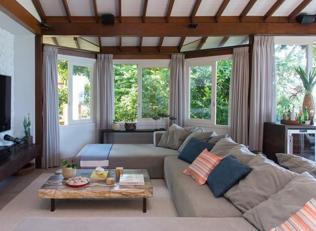 Também há passatempos para dias de chuva: o agradável canto da TV tem um sofá de medidas generosas e clima acolhedor. Almofadas da Bali Express (Foto: Cacá Bratke/Divulgação | Produção Deborah Apsan)