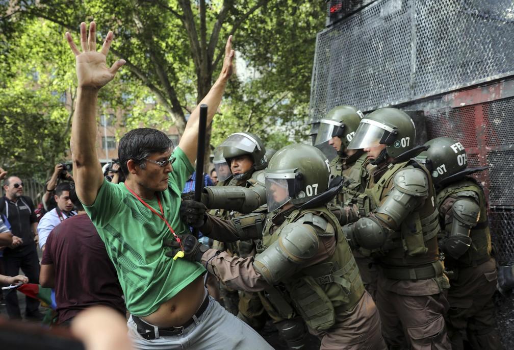 Homem é detido durante protesto em Santiago, no Chile, neste sábado (26) — Foto: Rodrigo Abd/AP Photo