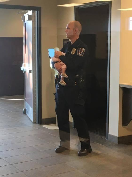 Policial e bebê na delegacia (Foto: Reprodução Facebook)