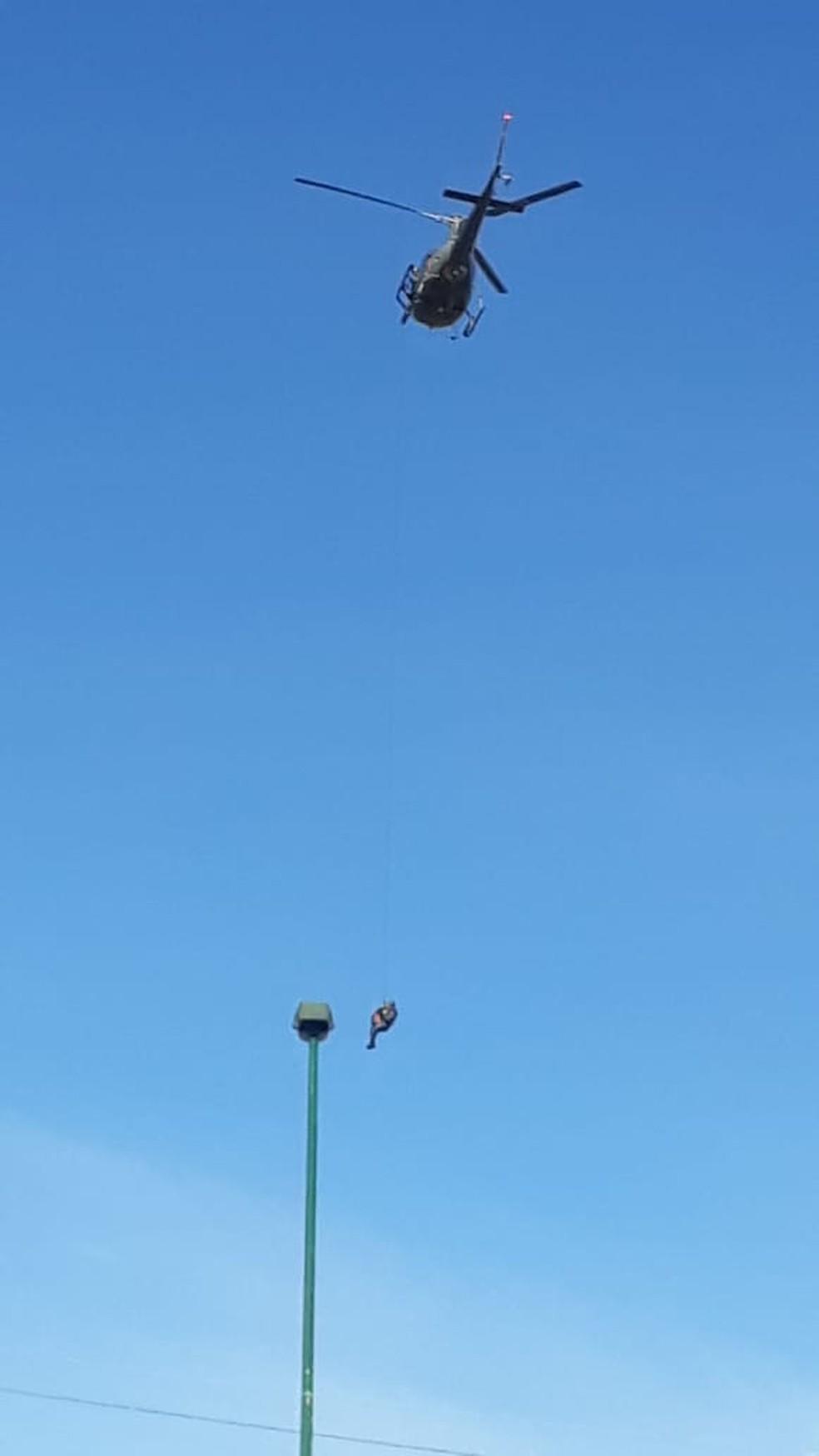 Homem foi içado pelo helicóptero da Polícia Militar — Foto: PM/Divulgação
