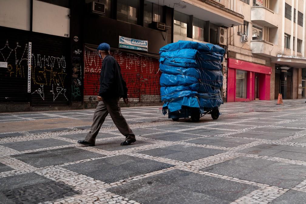 Homem caminha em rua com lojas e barracas fechadas no Centro de São Paulo.   — Foto: Marcelo Brandt/G1