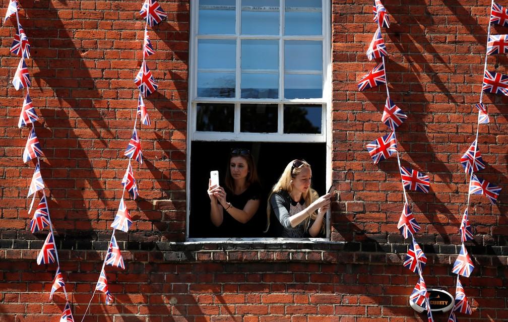 Mulheres fotografam de janelo o ensaio para o dia do casamento real em Windor, na Inglaterra (Foto: Damir Sagolj/Reuters)