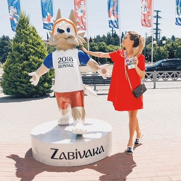 Carol Cabrino, mulher de Marquinhos, aproveitou para conhecer as praias de Sochi e fazer foto com o mascote à bordo de sandálias Chanel e bolsa Louis Vuitton (Foto: Reprodução/Instagram)
