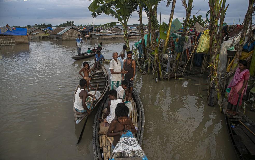 Indianos se abrigam em barcos ao longo das casas submersas pelo transbordamento do rio Brahmaputra, em Assam, no dia 16 de julho. Milhares estão desabrigados pelas inundações na região — Foto: Anupam Nath/AP