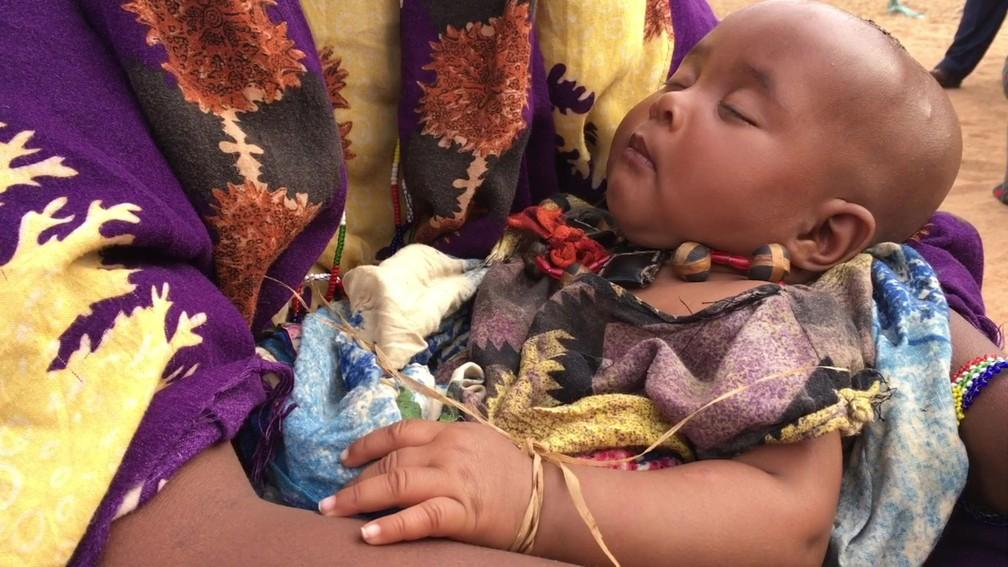 Para mostrar que a menina está noiva, o pai do futuro noivo amarra uma 'daraaraa' (espécie de pulseira de palha) no pulso dela — Foto: BBC