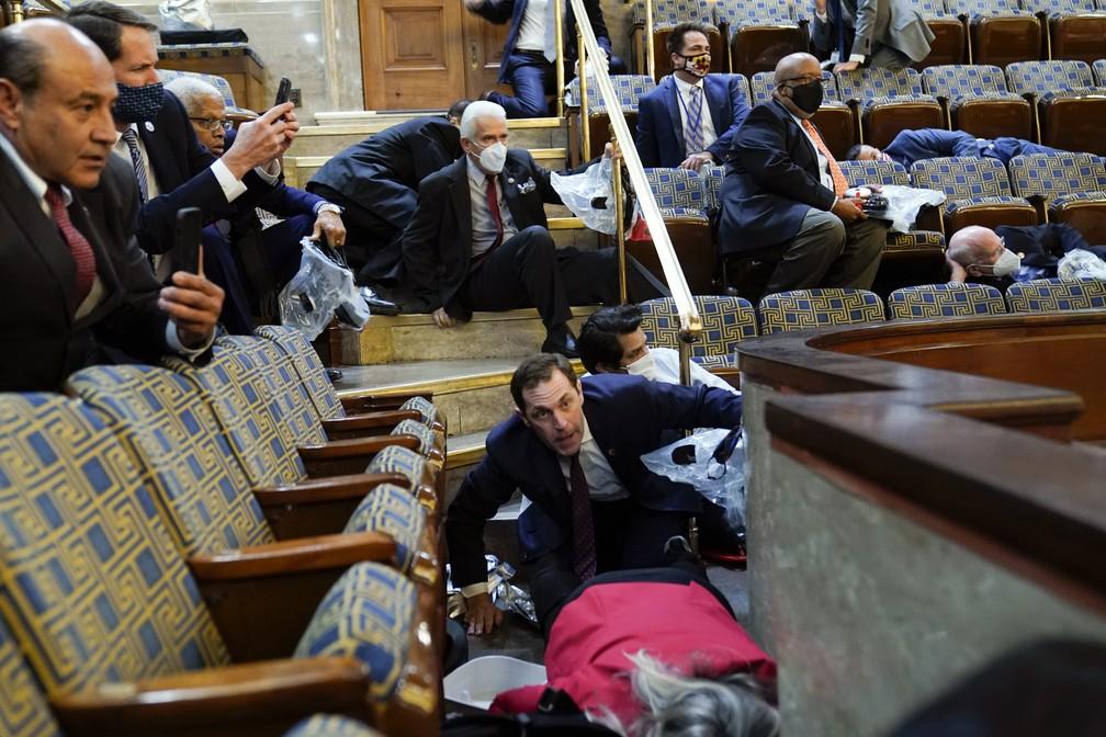 Pessoas se deitam no chão e nas escadarias da galeria do Senado dos EUA no momento em que manifestantes tentam entrar no Capitólio, em Washington — Foto: Andrew Harnik/AP
