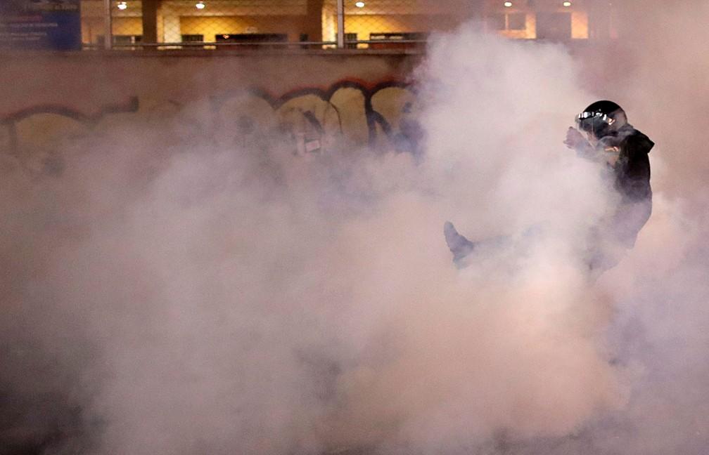 Membro das forças de segurança é visto em meio à fumaça provocada por gás lacrimogêneo em protesto de apoiadores de Carlos Mesa protestam em La Paz, Bolívia, na segunda-feira (21)   — Foto: Ueslei Marcelino/ Reuters