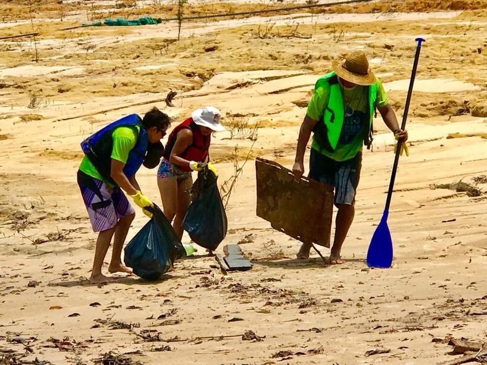 Grupo recolhe lixo das margens do lago durante períodos de cheia e vazante — Foto: Divulgação/Grito D'água