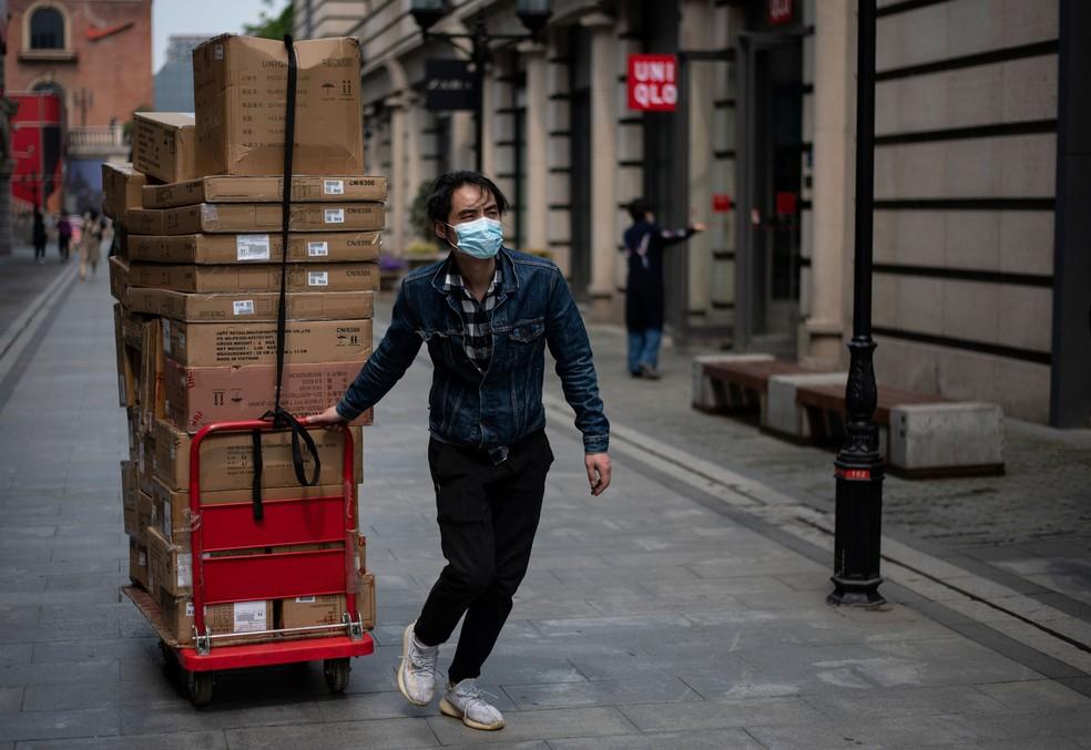 Trabalhador com máscara puxa um carrinho com mercadorias em rua comercial de Wuhan, na China, nesta sexta-feira (3) — Foto: Noel Celis / AFP
