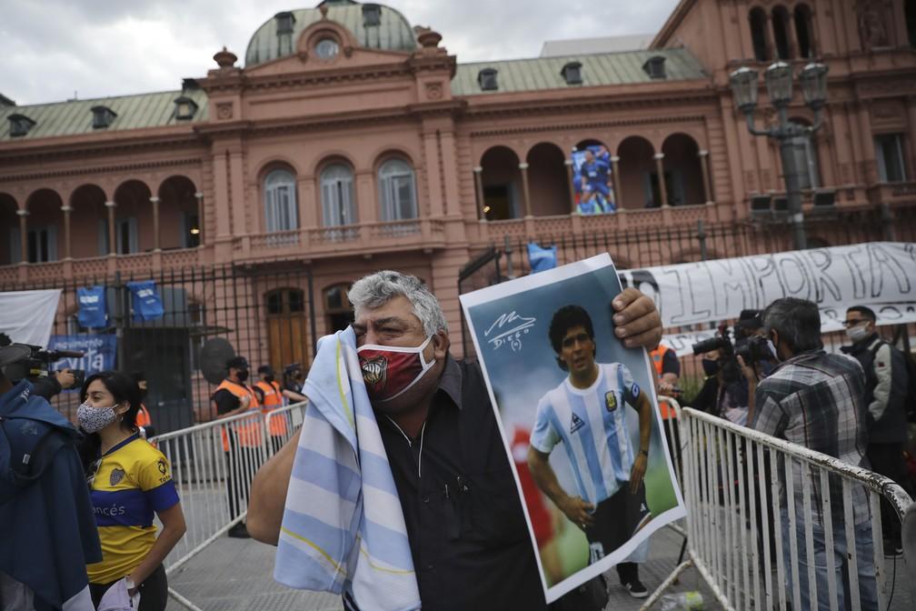 Argentino segura pôster de Diego Maradona e chora em frente à Casa Rosada, sede do governo argentino onde o corpo do ídolo é velado — Foto: Rodrigo Abd/AP