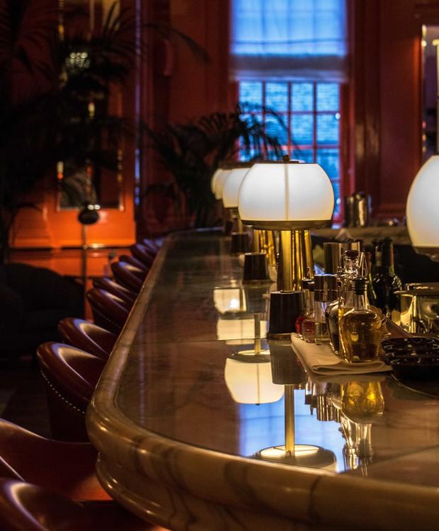 A bancada de mármore reflete o brilho da luz dos abajures vintage (Foto: The Coral Room/ Reprodução)