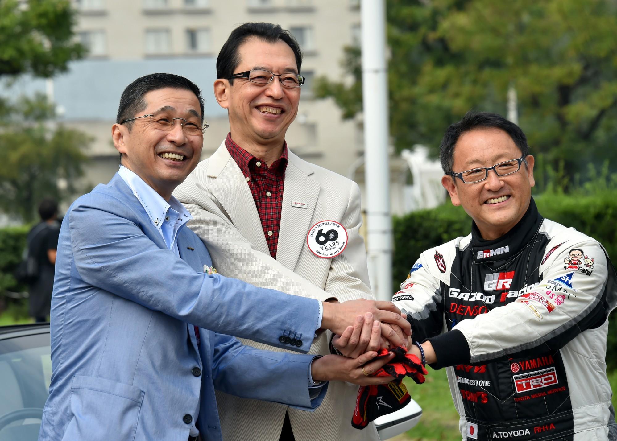 Hiroto Saikawa (esq.), então COO da Nissan, posa com Fumihiko Ike (centro), membro da mesa diretora da Honda, em comemoração dos 60 anos do Salão do Automóvel de Tóquio em 2015 (Foto: Getty Images)