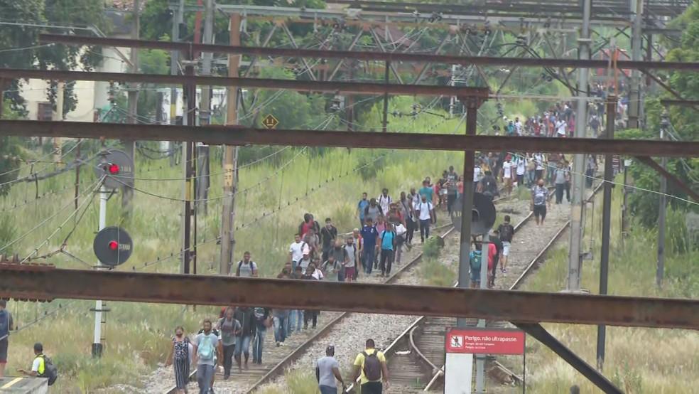 Passageiros caminham nos trilhos entre as estações Padre Miguel e Realengo da Supervia — Foto: Reprodução/ TV Globo