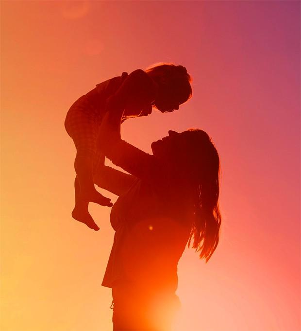Mãe segurando bebê no alto com filtro rosa (Foto: Thinkstock)