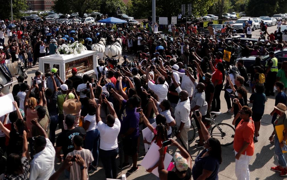 Multidão acena durante a passagem de carruagem que transporta o caixão de George Floyd no cemitério Houston Memoria Gardens, em Pearland, Texas, na terça-feira (9) — Foto: Reuters/Carlos Barria
