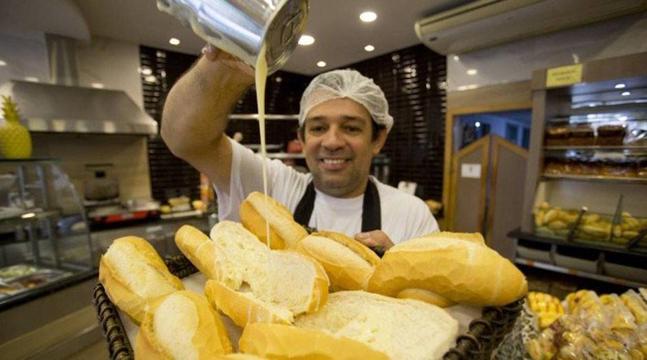 Na padaria Flor da Tijuca, o padeiro Ianaldo Alves coloca leite condensado no pão francês (Foto: Reprodução/Agência O Globo)