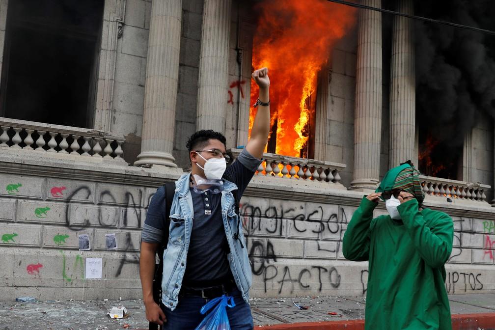 Manifestante faz gesto diante de janela incendiada no Congresso da Cidade da Guatemala neste sábado (21) — Foto: Luis Echeverria/Reuters