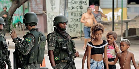 A Praça Miami é o coração da Vila Kennedy; homens do Exército patrulharam a região durante o dia, fizeram revistas e orientaram moradores. Morador revistado três vezes disse que pediria música. Soldado riu. (Foto: Brenno Carvalho/Agência o globo)
